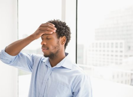 Young concentrating businessman leaning with his back against a window while holding his head in the office